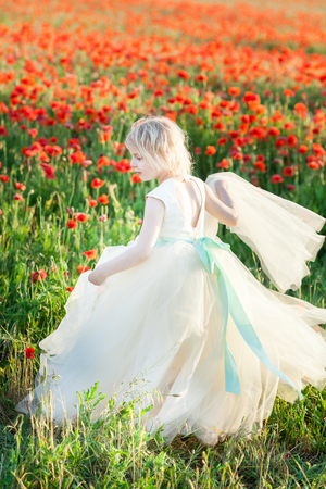 girl model, poppies, childhood, fashion, nature and summer concept - a young girl - an angel in a festive white dress walks through a field of poppies, holding the hem of her dress with her hand