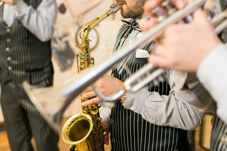 music, show business, orchestra concept. men from jazz band dressed in marvelous black costumes with thin white strips are playing sax of golden colour and silver trumpet