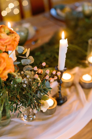 dating, hospitality, comfort concept. tall slim candle that is standing in black holder surrounded by lots of small ones, placed by it on the table with romantic setting of flowers and dishes