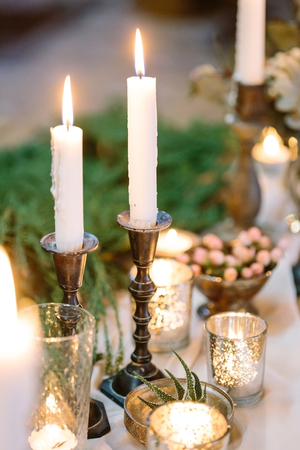 comfort, cosiness, entertainment concept. two tall white candles are burning in their holders, surrounded by different small ones, there is wonderful tableware