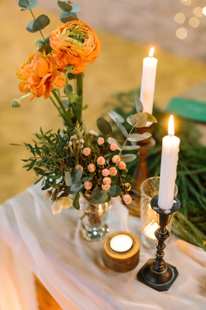 feast, present, floral design concept. on thick drapping two small extremely beautiful posies with bright orange roses, lots of various leaves and small light pink berries, they are placed by candles Stock Photo