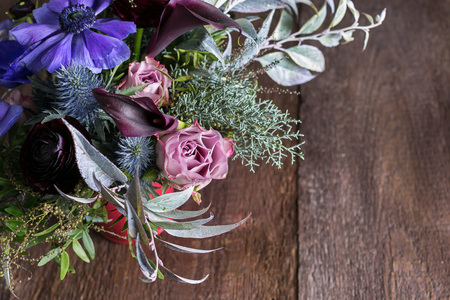 floral design, decor, sentiments concept. there is lovely bouquet made of ballet pink roses, purple anemons, amazing dark maroon persian battercups, embellished with different leaves and thistles