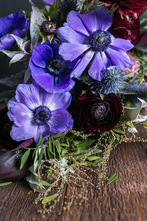 nature, flower arranging, hobby concept. close up of great lilac anemons with puffy black centers that placed in the bouquet decorated with various leaves and battercups