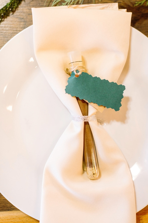 celebrating, tableware, culture concept. top view of the white flat plate for the second course with textile napkin of ivory colour with emerald card for name of the guest