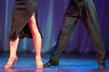 passion, showing, clothes concept. man and woman are performing a latin american dance on the stage, they are perfectly dress in stilish black and dark blue coloures