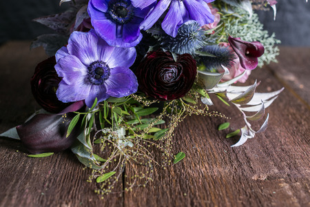 growing, decoration, romance concept. on the wooden table there is adorable bouquet of flowers, wonderful maroon battercup is surrounded with lilac abemons Stock Photo