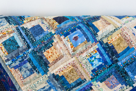 hobby, free time, quilting, home cosiness, background, sewing concept - bright blue blanket made of ornate satin patches in geometric forms with such various patterns like flowers, dots and doodles