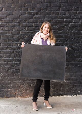 arts and craftsm applied art, lifestyle concept. on the background of painted brick wall there is cheerfull woman dressed in autumn clothes, she is holding blackboard for drawing with chalks