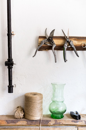 working, arts and crafts, supplies concept. there is a still life composed of equipment of workman on the white background of wall, there are pruners, rough twines and other stuff