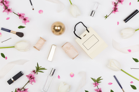 birthday, women day, party concept. top view of popular presents for women such as perfumes, pomades and other cosmetics that placed among tulips and oriental cherry