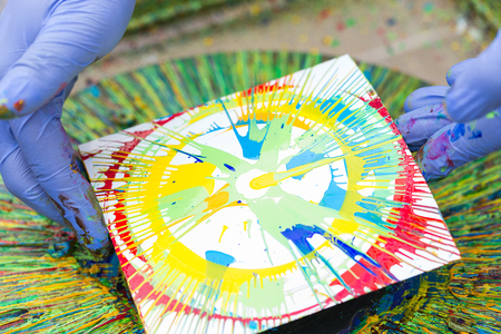 artwork, equipment, creation concept. in the arm of artist in blue rubber gloves there is white square sheet of paper with imprint created with shining bright paints of different coloures