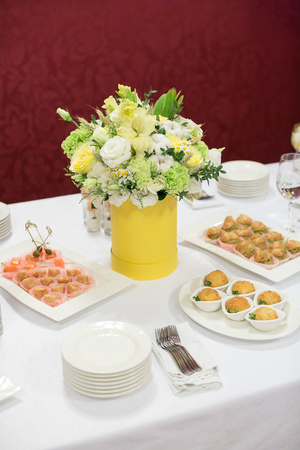 food, dinner, flower arrangement concept. on the center of the table covered clean white tablecloth there is marvelous bouquet of delicate white roses that look like whipped cream Stock Photo