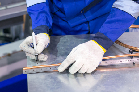 clothes, work, manufactury concept. there is male specialist who wearing gloves and blue uniform made of tight fabric, he is marking long thick copper wire with black permanent marker Imagens - 93282689