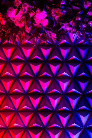 party decoration, wedding design, abstract background concept. in the bright lights of red and blue colores white paper pyramids and bunches of flowers are getting delicate pink and light blue