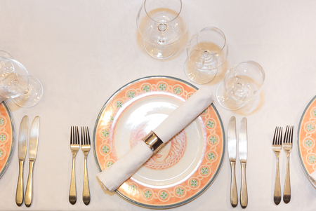 Tableware, catering, design concept. Top view of served place of restaurant with flat plate decorated by floral patterns, set of silverware, white napkin and three different glasses Stock Photo
