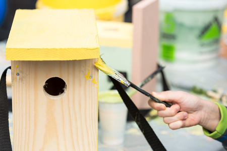 artist job, drawing, repairing concept. close up of nesting box that is not prepared for using yet, in the soft arm there is a brush for painting this wooden box in sunny yellow color