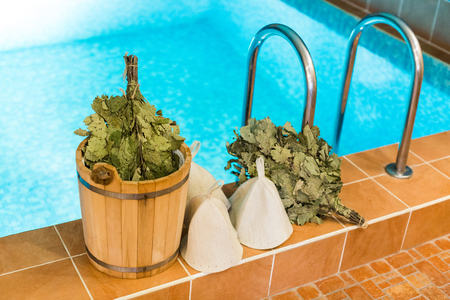 spa, leisure time, healthy life concept. on the edge of swimming pool with clean water there is set for taking bath with fellows that includes few brooms, white wool hats and bucket