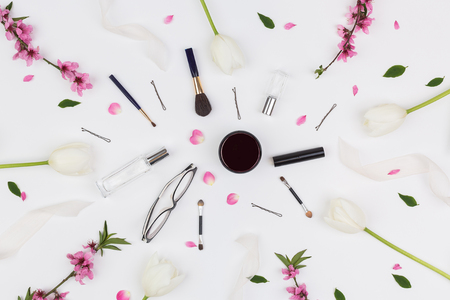 cosmetology, womanhood, beauty concept. on the snowy white surface there are a frame created of collected flowers and there is mess made of different stuff for make up