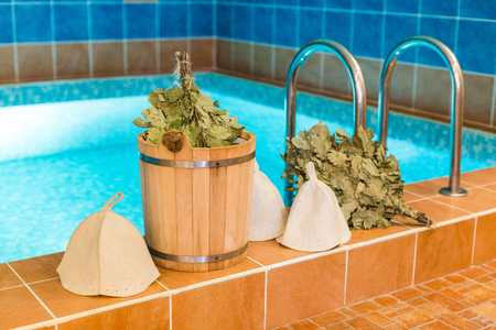 spa procedure, beauty, holidays concept. by the pool with clean water there is traditional russian supplies for taking steam bath, among them you can find hats ans brooms