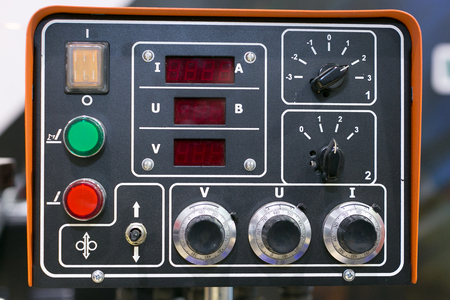 electricity, manufacturing, instrument concept. there is electronic dashboard for working with different devices, it has few buttons of different colours, small red screens for results