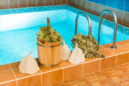 equipment, tradition, rest concept. there are the most popular supplies for steam bath such as hats, brooms of collected oak branches and wooden bucket with cold water Stock Photo