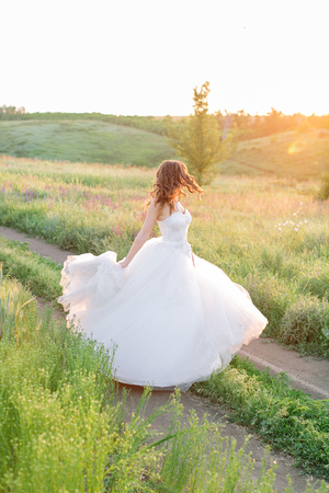 wedding day, beauty, nature concept. in the middle of the field there is an amazing woman wearing white bride dress, she is spinning around herself and sequins are shining in the light of sun Archivio Fotografico