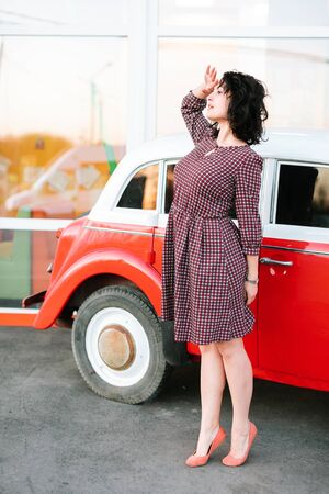 freedom, travelling, transportation concept. in the parking lot there is a beautiful but really old car of bright red color, yound tall woman is standing by it, she is looking straight forward