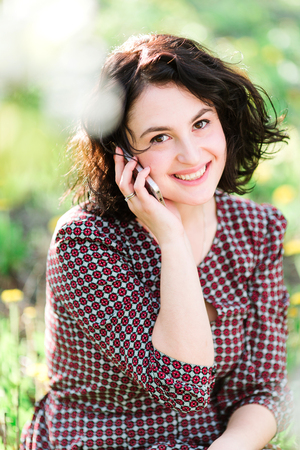business, womanhood, contact concept. there is beautiful woman in the dress with small red flowers, she is listening to somebody by her phone and smiling happily, her dark eyes are glowing Stock Photo