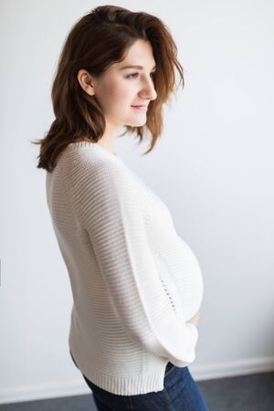 fashion, style, pregnancy concept. there is a young woman that looks gorgeous, dressed in casual style, knitted comfortable sweater and jeans, she has beautiful profile and chestnut colored hair Фото со стока