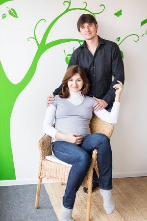 family, connection, relations concept. on the background of wall with green painting of tree there is a young couple who are preparing to be parents, pregnant lovely woman is sitting in the chair
