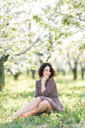 beauty, nature, time of year concept. soft spring sunlight is falling through the branches of different garden trees, it is falling on the lovely face of charming woman in dress Фото со стока