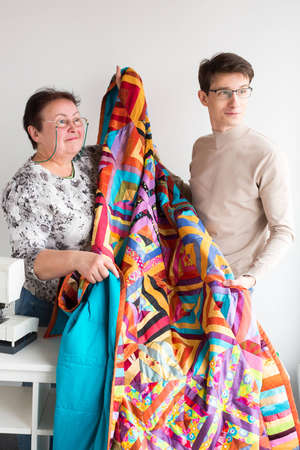 occupation, small business, happiness concept. there is a couple of coworkers of atelier, young designer and old seamstress, both are wearing eyeglasses and smiling calmly Фото со стока