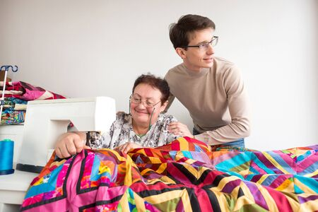 family relationships, occupation, business concept. there is a young and attractice man who is standing by his grandmother, she is stitching great gorgeous blanket sewing of bright pieces of fabric