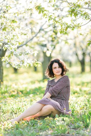 gardening, walking, lifestyle concept. in the shadow of apple trees among yellow little flowers there is charming woman with short black curly hair and pail complexion