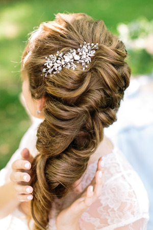 style, femininity, brides hairstyle concepr. in soft curly light brown hair of young woman there is shining barrette with diamonds in form of leaves and flowers Stock Photo