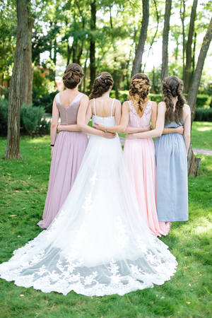 celebration, engagement, woman frienship concept. backs of four young slim women, happy bride in traditionaly white dress and her friends, standing backs in the summer park full of trees and bushes Stock Photo