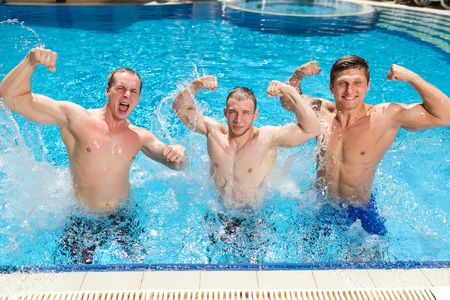 sport, health lifestyle, summer concept. three strongly built men are standing in the outdoor swimming pool and posing as athletes or wrestler showing their great muscles Фото со стока