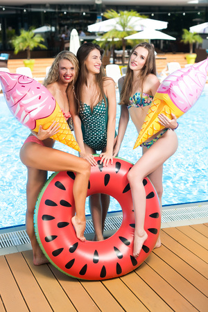 beauty, relaxation, party concept. there is a company of young slim girls who are standing by the swimming pool, they are dressed in stylish bikinis and holding balloons and rubber ring