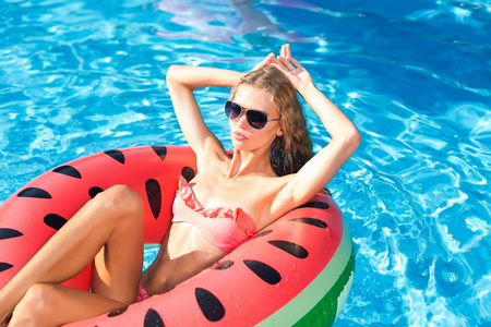 summer, resort, style concept. pretty girl is sitting on the rubber ring designed as a watermelon slice, she is posing and having sunbathes dressed in pink bikini
