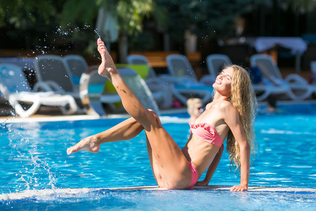 fun, gladness, resort concept. a wonderful cheerful girl with light face and long hair is sitting on the edge between two swimming pools separated with barrier, she has long gorgeous legs Фото со стока