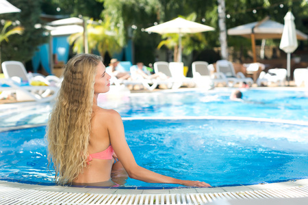 recreation, freedom, lifestyle concept. on the background of swimming pool and people under umbrellas who are lying on the deck chairs, there are a lonely girl with blond hair and elegant profile