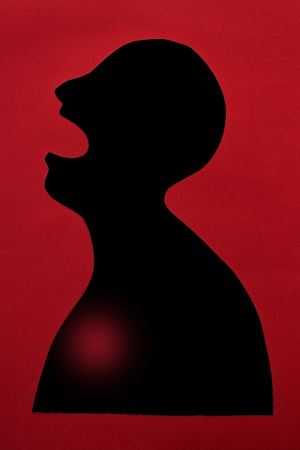 concept of human disease diagnosis and pain localization on silhouette - contour of abstract african man with opened mouth and heart failure, isolated on red background, top view, flat lay