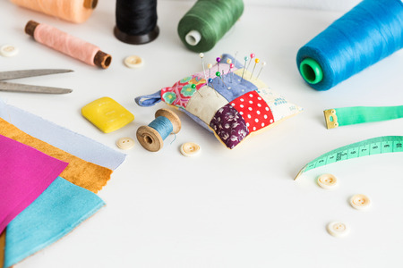sewing tools close-up, patchwork, tailoring and fashion concept - working environment on a white table, thread spools, buttons, meter, pincushion, scissors, pieces of colorful patchwork fabric, soap Фото со стока