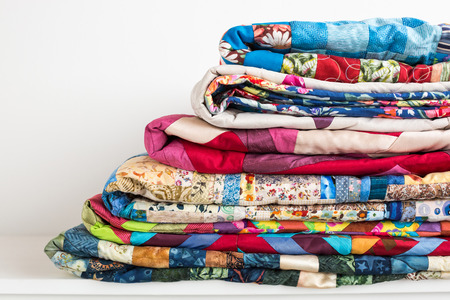sewing, patchwork and fashion concept - beautiful colorful quilts were neatly folded and stored in several rows in height for storage, sale of finished textile stitched products on white background Фото со стока