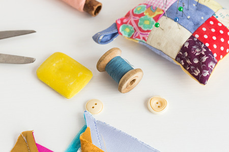 sewing, patchwork, tailoring and fashion concept - closeup tools on white desk in studio, pincushion, blue and pink threads spools, white buttons, scissors, soap, pieces of colored patchwork fabric