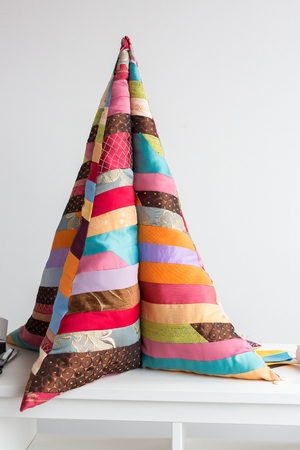 handmade, interior, decoration concept. there is a tall and soft construction in form of christmas tree but made of bright wonderful blanket sewd of different in colours and patterns patches
