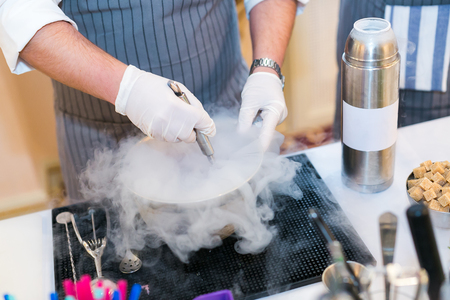 barman cooks molecular cocktail with use of liquid nitrogen. alcoholic molecular beverages for a party.