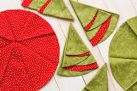 patchwork and sewing concept - macro of decorative red-and-green napkins on whitewashed wooden floor, festive embroidered towels in shape of circles and Christmas trees, top view, flat lay Reklamní fotografie