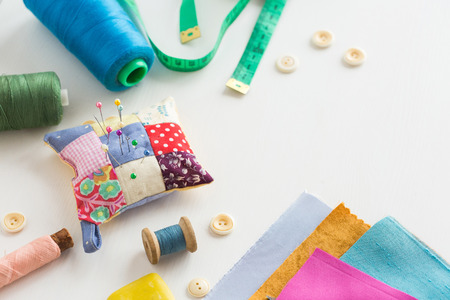 needlework, craft, sewing and tailoring concept - tools closeup on white desk, measuring meter, blue, pink and green threads in spools, scraps of colorful fabric, pincushion, white buttons and soap
