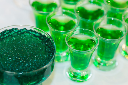 vivid green cocktails with molecular caviar close up, glowing drinks of the fluorescent bar. Фото со стока